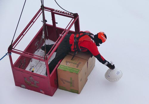 Ship crew is deployed to position the boxes of small 'seaworthy vessels' and the tracking buoy onto the ice. (Photo Bill Schmoker)