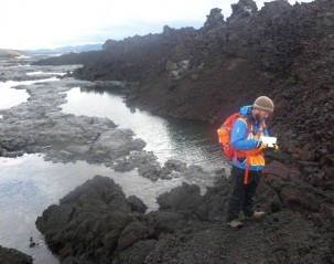 A graduate student takes notes about how the new lava flow (dark brown/black) is interacting with the  old flow (light gray) and  the river.