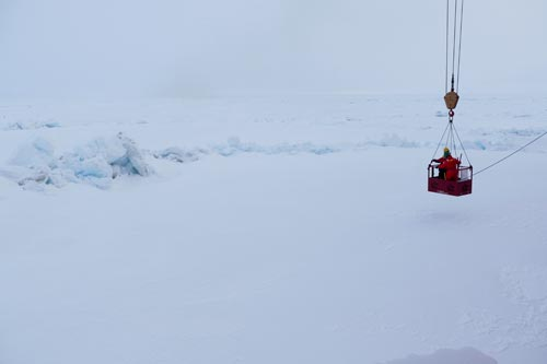 The 'man-basket' lowering Tim Kenna and crew member to the ice via crane to do sampling from a pressure ridge. (photo Bill Schmoker)