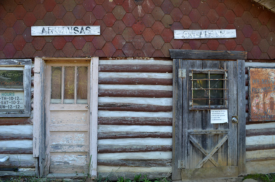 On a back road, a rural nightspot built of local logs straddles the state line so neatly, you can enter in one state and leave in another (in more ways than one). As you travel westward from Arkansas into Oklahoma, the land flattens, climate dries, and trees become less common.