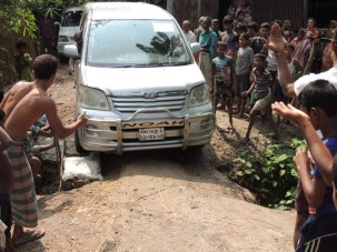 One of our cars drives over the makeshift road repair of a sandbag, bricks, wood and rebar while the entire village looks on.