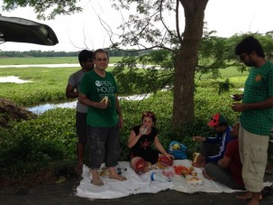 Eating a picnic lunch in the field at side of the road.  Vans on either side protected us.  We usually had bananas, oranges, crackers, cakes and on this day pineapple as well.