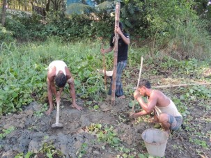 The three-person drill team preparing the site.  Digging a post hole with rebar, inserting the bamboo pole and digging the mud pit with a kudali.