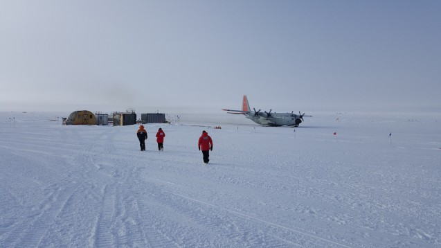 On the flight to the South Pole the LC130 hercules aircraft is the rear right parked at the edge of the skiway. The ice pod is on the far side the South Pole station. Team members Kirsty, Tej and Fabio are heading towards the South Pole passenger terminal waiting to reboard. (Photo N. Brady)