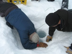 Extracting the sediment core starts with clearing out a hole through the lake's 3-foot-thick ice. (Photo courtesy of William D'Andrea)
