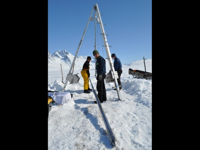 Researchers standing on the frozen lake inspect the coring tube that will be lowered to the lake floor and driven into the sediment below.  (Photo courtesy of William D'Andrea)