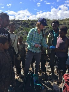 Penn State PhD student Beth Hoagland explains the process of measuring turbidity to children from a community near the mine in January 2016.