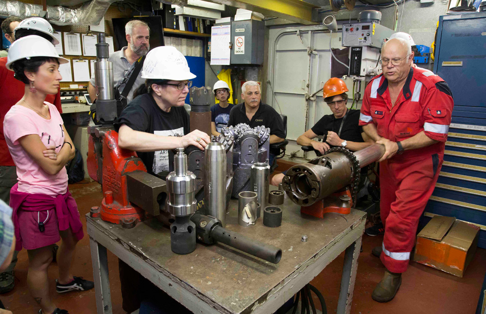 Bubba Attryde, a core technician, shows scientists on the <i>Joides Resolution</i> some of the ship's drilling tools. Tim Fulton/IODP