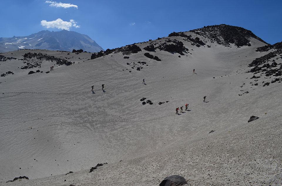 Team members trudge upward through fine pumice debris, on their way toward the source crater.