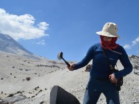 The researchers take numerous lava samples for later analysis. University of Chile graduate student Rayen Gho attacks a boulder.