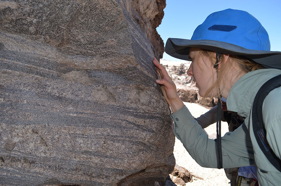 Lamont-Doherty postdoctoral researcher Megan Newcombe examines a lava block that developed distinct flow bands as it oozed along.