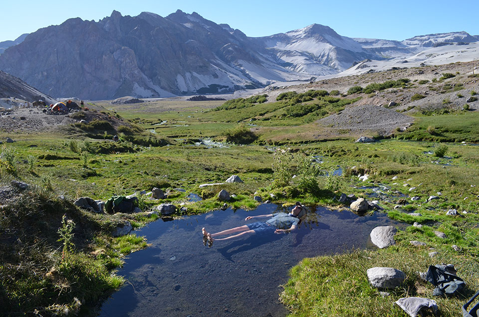 At a rare oasis where pasture has managed to re-emerge, warm springs are fed either by still-cooling lava or continuing magmatic activity. University of Michigan geologist Adam Simon takes his only bath of the trip.