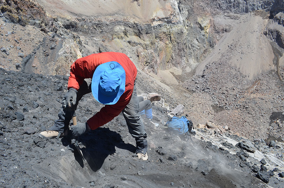 At the edge of the abyss, Ruprecht and Hammer remove a sample of the terminal scoria—the final layer of debris spit out during the volcano's last gasps.