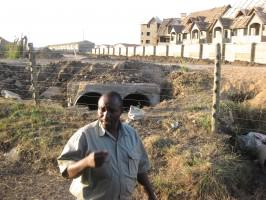 Housing built just beyond the NNP fence; Southern Bypass is to be built along the dirt strip that still separates them. In the foreground is Michael Wanjau, then-Senior Warden for NNP. Photo: Glen Hyman