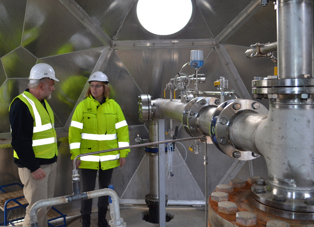 Martin Stute, a Lamont-Doherty Earth Observatory scientists who will be giving a live-streamed seminar about the CarbFix Project, talks with Edda Sif Arradotir of Reykjavik Energy in front of the piping system that pumps emissions back underground. Photo: Kevin Krajick