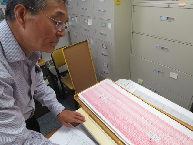 "Seismologist Won-Young Kim pulls out the original paper seismogram showing the jet impacts, and subsequent collapses, of the World Trade Center towers. ""It was a very painful day,"" he said. (Kevin Krajick)"
