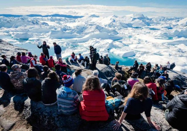 Participants in Students on Ice listen to scientist Maureen Raymo (top left) discuss climate change at the foot of Greenland's Illissaat Icefjord. (Image: Martin Lipman/Students on Ice)