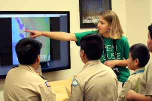 Anna Barth and a group of Boy Scouts looked for patterns in earthquake locations and sizes by watching years of eruptions compressed into a few minutes. The video they're watching is part of the Seismic Sound Lab's SeismoDome project.