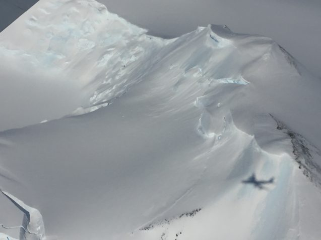 Mountains are buried under deep layers of ice. The shadow of the DC8 can be seen against the mountain. (Photo M. Turrin)