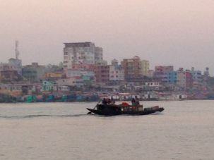 A set of colorful houses line the bank of the broad Meghna River. We continue south to find sampling sites.