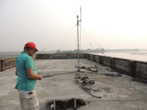 Humayun inspecting our equipment on the roof of a school on Polder 32. The tower is a meteorological station and our GPS antenna is on the back wall.