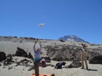 Elise Rumpf launches a small drone with a camera over Chile's Quizapu volcano. Photo: Kevin Krajick