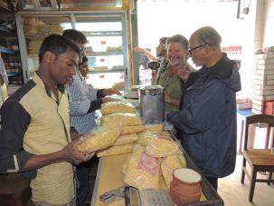 Chris smiling broadly as he and Humayun buy 11 lbs of Jordibaja, a local Kushtia snack food from the most famous bakery that makes it.