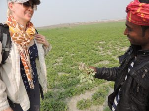 A local farmer shows Liz the peanuts he is growing on the char (behind them). Peanuts and lentils are common winter, or rabi, crops on the higher, drier parts of the char. The freshest peanuts we ever ate.