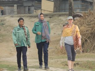 Liz in Rajshahi walking back to our group protected by two policewoman that were part of our escort during a quick visit back to our van.