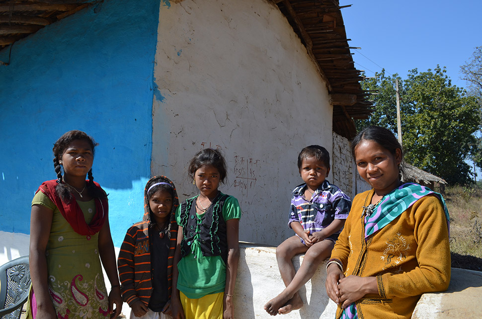 """In Botalbehra, we met Geeta Dhurve (right) with her son and some young neighbors. Like many, she is a member of the once-nomadic Baiga forest people. Now everyone has a house and garden, and kids attend the village school. """"We don't know anything about what comes out of the jungle,"""" she said."""