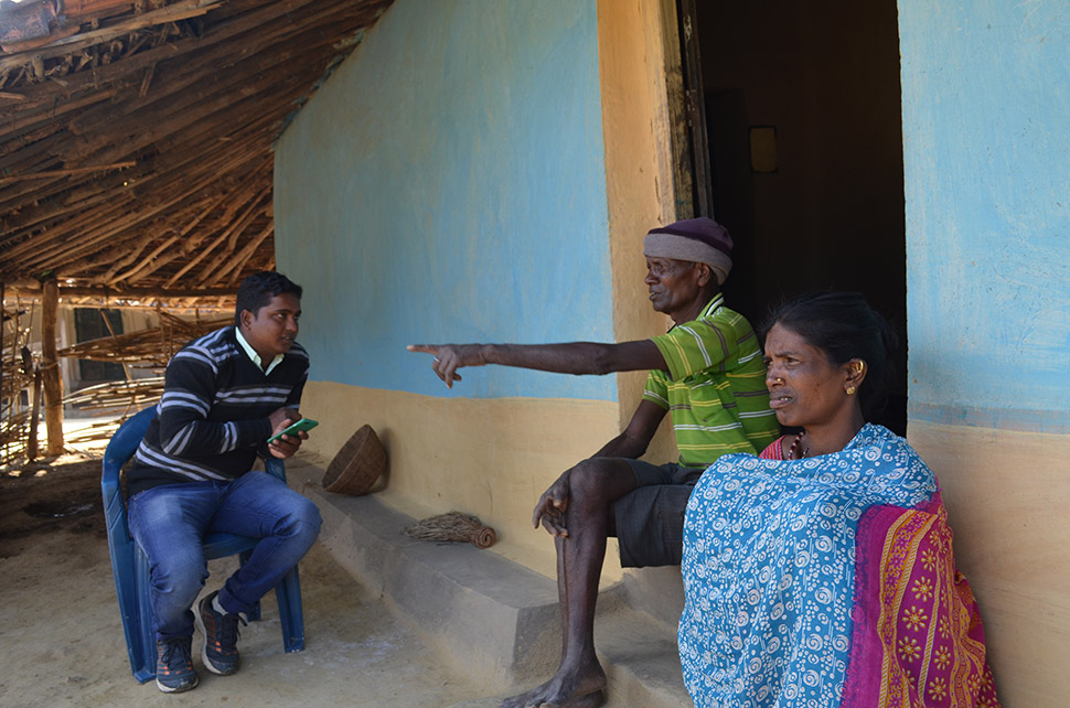 """Near the village of Khirgitola, a pollster (left) interviews Jaani Bai and her husband, Nazar Singh Markam. Relocated three years ago, they own a substantial family compound and 2 acres. In line with recently instated legal protections, they were paid the equivalent of $15,000 each and allowed to move wherever they wanted. When asked why they moved, they replied only: """"The government told us to."""""""