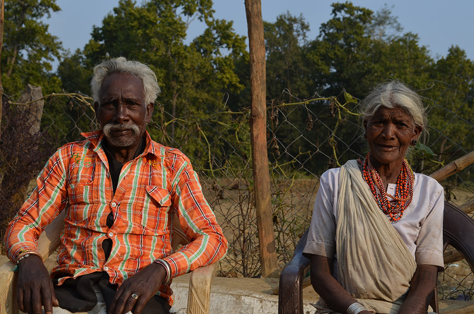 After a life in the forest, a resettled Baiga couple, Bajari (left) and Chaeti Bai, sit for a portrait in their family compound.