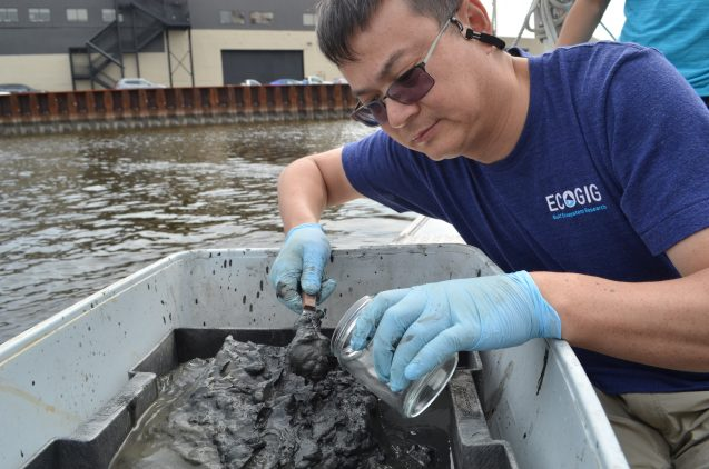 Yan samples the muck. It will go back to the lab for analysis.