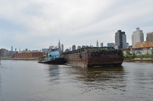 A tug moves an empty barge up Newtown Creek.
