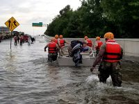 soldiers move through flooded street