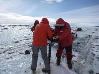 Team members taking a short ice core to study properties of sediment coming from the East Antarctic ice sheet. (Photo: Mike Kaplan)