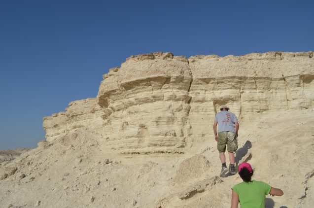 Kiro and Mordechai Stein of the Geological Survey of Israel approach a Cliffside deposit in the Israeli desert.