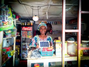 A shop owner with one of Easy Solar's lanterns. / Photo: Nthabiseng Mosia