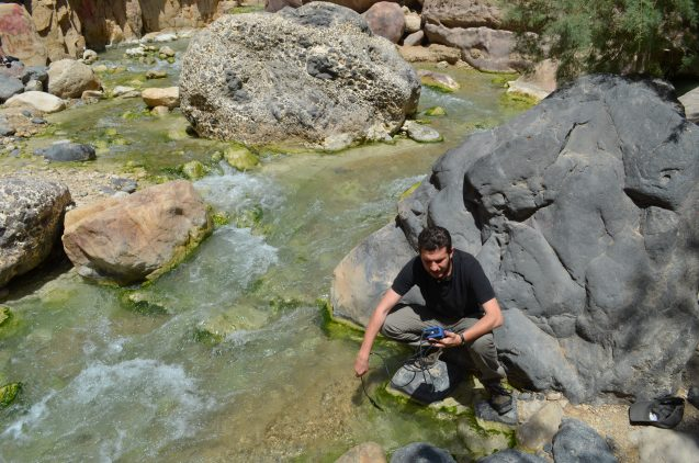 Mohamad Alqadi, a Jordanian PhD. student at the University of Munich, tests pH and temperature of stream water in a canyon.