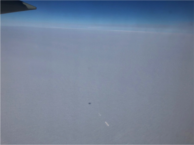 View out of the LC-130 during Monday afternoon's flight. The grey spot is the shadow of the plane. Photo Credit: Alec Lockett