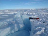 A researcher investigates a channel in the Greenland ice