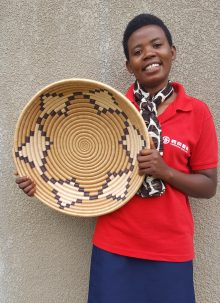 One woman holds up a large, woven basket that takes more than four days to make.