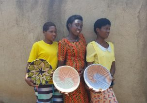 Three women participating in the Connect to Learn basket-weaving vocational program display their colorful baskets.