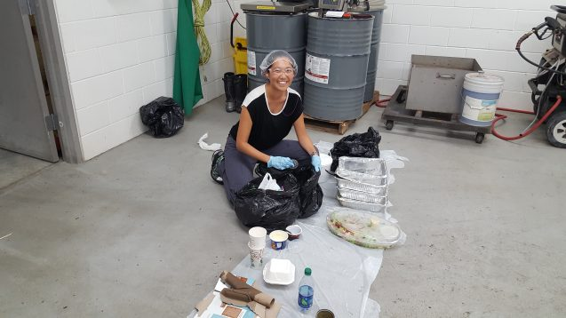 Asami sitting on the floor with an open trash bag on a tarp, sorting types of waste. She is wearing a hair net, goggles, and gloves, and she is smiling.