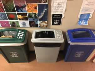 Paper recycling, trash, and glass/metal/plastic recycling bins with new tops that have the same square-shaped openings.