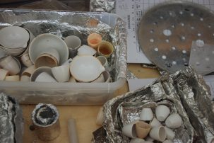 Bins of small white ceramic bowls used for burning samples.