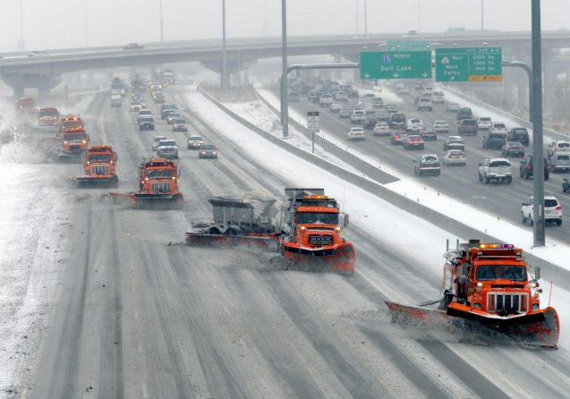 Snow plows in tandem formation deicing a multilane highway.