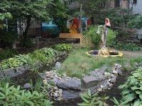 A garden featuring a small pond with an island in the middle, a bench, and a mural of Frida Kahlo in the background.
