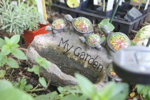 "A rock engraved with ""My Garden"" nestled in soil, with small stone turtles marching along it."