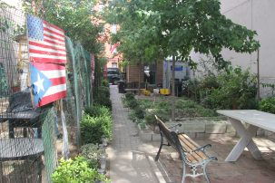 A garden with a cobblestone pathway, the left of which has a fence where American and Puerto Rican flags hang. On the right, garden beds and a picnic table.